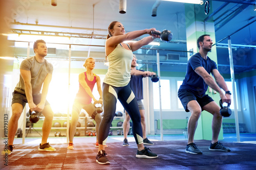 Fotografia  group of people with kettlebells exercising in gym