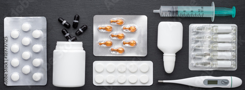 Thermometer, nasal drops tablets and ampoules with medicine on dark slate board Canvas-taulu