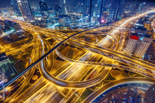 obraz dibond Aerial view of big highway interchange with traffic in Dubai, UAE, at night. Scenic cityscape. Colorful transportation, communications and driving background.