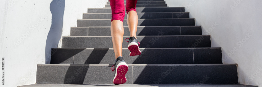 Fototapeta Hiit workout cardio running up the stairs training. Staircase climbing run woman going run up steps panorama banner. Runner athlete doing cardio sport workout. Activewear leggings and shoes.