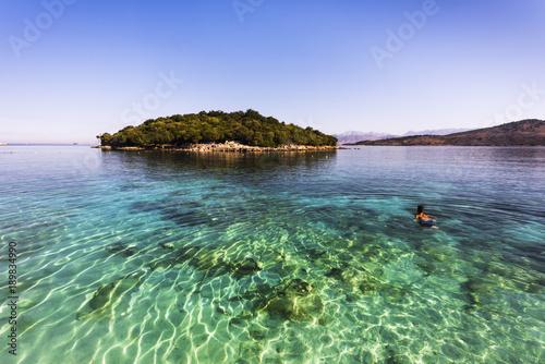 Photo Ksamil Beach - Sportive man swimming to an idyllic island in sunrise atmosphere,