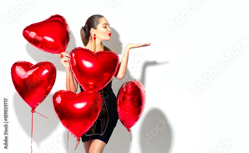 Valentine's Day. Beauty girl with red heart shaped air balloons having fun, isolated on white background