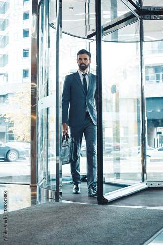 Fotografía  Businessman in a fromal suit in a business center enter the building with briefc