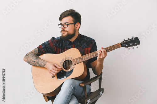 In de dag Art Studio Young guitarist hipster at home with guitar on the chair isolated