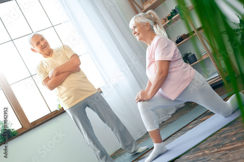Senior couple doing yoga together at home health care stretching leg ...