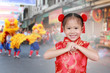 Leinwanddruck Bild - Little chinese girl in traditional Chinese cheongsam blessing for you in chinese new year festival.
