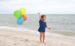 Portrait of asian little girl playing with colorful balloons at the beach.
