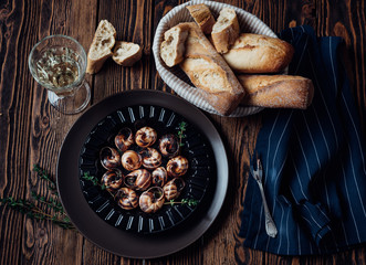 Escargot with glass of white wine and fresh baguette on a dark wooden background.
