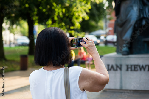 Photo Gdansk, Poland - August 10, 2017: Woman taking photo at her smartphone of statue of polish astronomer Jan Heweliusz