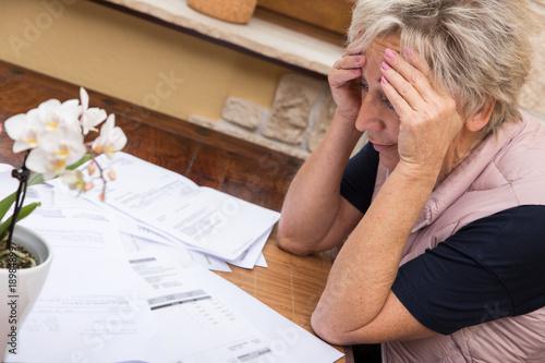 Fotografía  Ältere Frau sitzt vor vielen Rechnungen und ist verzweifelt, Konzept Geldnot und