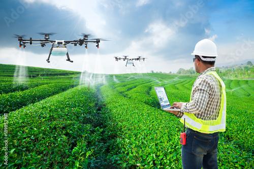 Photo  Technician farmer use wifi computer control agriculture drone fly to sprayed fertilizer on the green tea fields, Smart farm 4