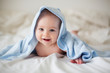 canvas print picture - Cute little baby boy, relaxing in bed after bath, smiling happily