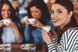 canvas print picture - Three young women enjoy coffee at a coffee shop