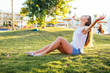 Young woman lying on green grassland and stretching her arms on sunshine
