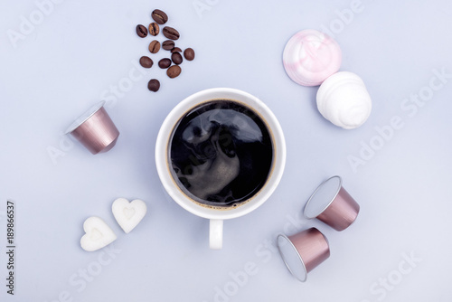 Top View Cup of Coffee Coffee Capsule Coffee Beans Sugar in Shape of Hearts Marshmallow Coffee Concept Background Blue Background Flat Lay