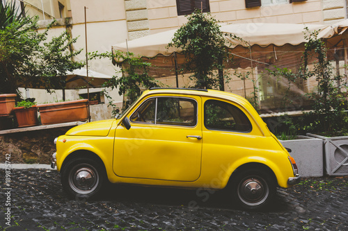 Deurstickers Oude auto s A yellow car in a small street in Rome