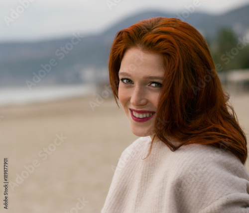 Fotografia A nice  girl with a beautiful smile is sitting on the beach