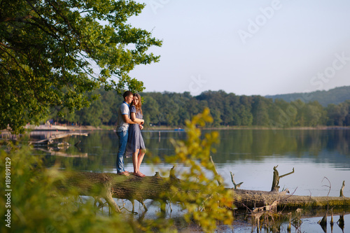 Canvas Prints Guilin Romantic beautiful couple in love standing alone on a tree that lies in a lake with blue water at sunset of the day