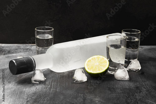 Photographie Cold vodka in shot glasses on a black background