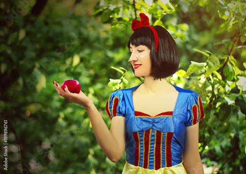 Fotografie, Obraz  Young beautiful snow-white close-up keeps a red poisoned apple against the backg