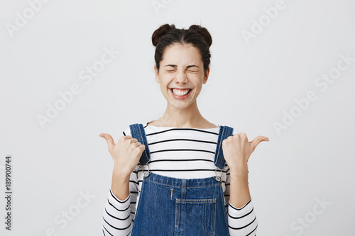 Positive funny brunette girl with hairbuns in striped top, clenching teeth in smile, closing eyes in joy points at copy space, poses at studio Canvas-taulu