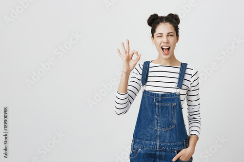 Positive funny brunette girl in denim clothes shows ok sign, blinks at camera, demonstrates that everything is fine, agrees Canvas-taulu
