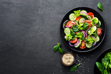 Fototapeta Healthy vegetable salad of fresh tomato, cucumber, onion, spinach, lettuce and sesame on plate. Diet menu. Top view.