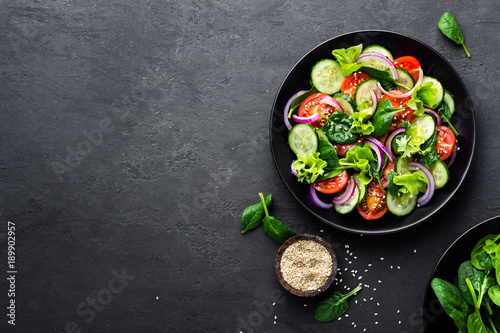 Fototapeta Healthy vegetable salad of fresh tomato, cucumber, onion, spinach, lettuce and sesame on plate. Diet menu. Top view. obraz