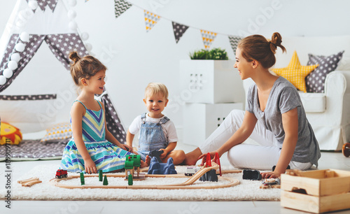 family mother and children play a toy railway in playroom.