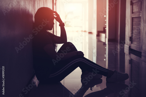 Fotografía  Silhouette of sad and depressed women sitting at walkway of condominium or office with backlit and lens flare,sad mood,feel tired, lonely and unhappy