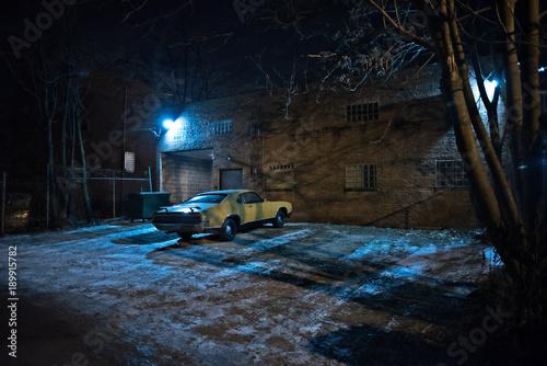 Fotografie, Obraz  Vintage muscle car in a dark Chicago city urban alley on a winter night