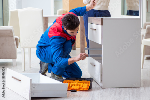Photo  Contractor repairman assembling furniture under woman supervisio