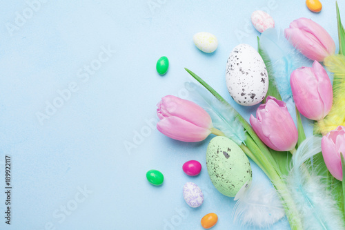 Greeting card for Easter. Tulip flowers, eggs and candy on blue table top view.