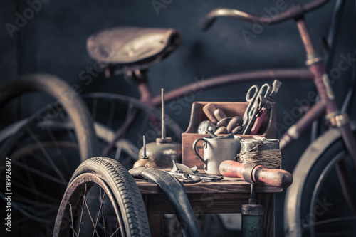 Tuinposter Fiets Old bicycle repair workshop with wheels, tools, and rubber patch