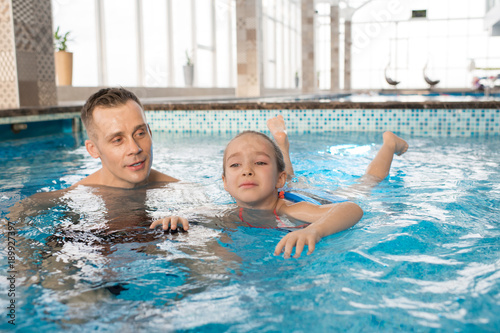 Fototapeta Portrait shot of handsome man teaching his frightened little daughter to swim in modern swimming pool with panoramic windows obraz na płótnie