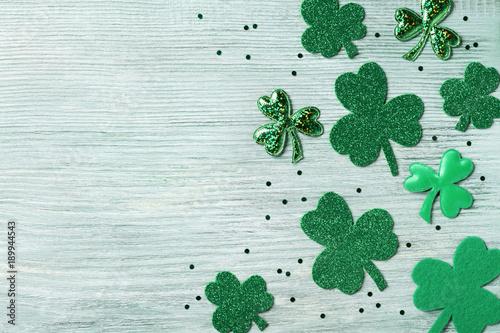 Obraz na plátně Saint Patricks Day background with green shamrock on white rustic board top view