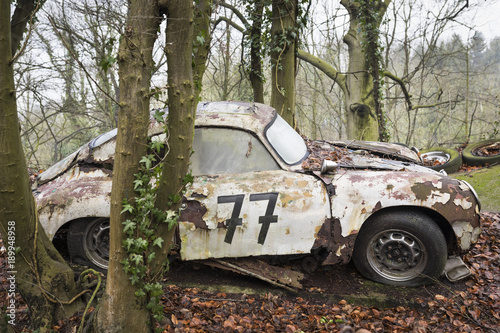 Photo  Abandoned sports car decaying in a forest