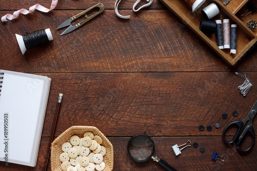 Flat lay aerial image of fashion designer items background concept.Top view sewing accessory or tailor equipment on modern rustic brown wooden at home office desk studio.Crafting tools in work shop.