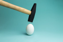 Egg And Hammer Hovering Over It, Before The Hit. One Egg And Hammer On Blue Background