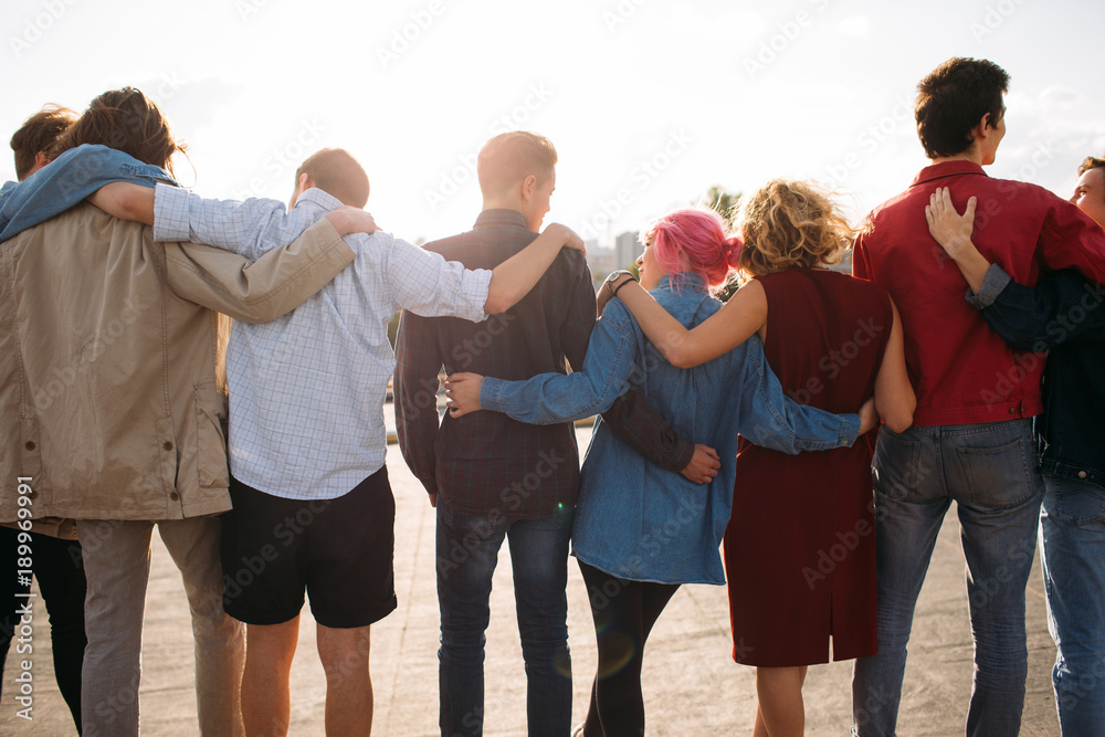Fototapeta Back view of young diverse people group. Arm around. Unity support. Friendship together