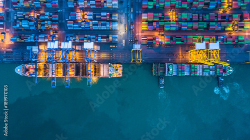 Fotomural Aerial view container cargo ship working at night with industry crane, Container cargo ship business commerce import export logistic, Logistic and transportation of International container cargo ship