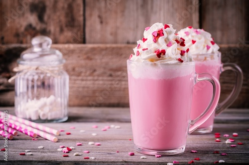 Pink hot milk with whipped cream and sugar hearts in a glass mug for Valentine Day