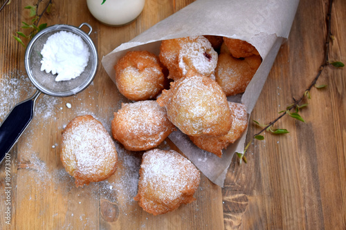 French doughnuts Beignet covered with sugar powder on a wooden table