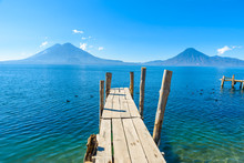 Wooden Pier At Lake Atitlan On The Beach In Panajachel, Guatemala. With Beautiful Landscape Scenery Of Volcanoes Toliman, Atitlan And San Pedro In The Background. Volcano Highland In Central America.
