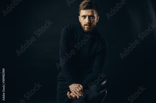 Fotografija  Bearded man wearing black looking unemotionally at camera on black background of studio