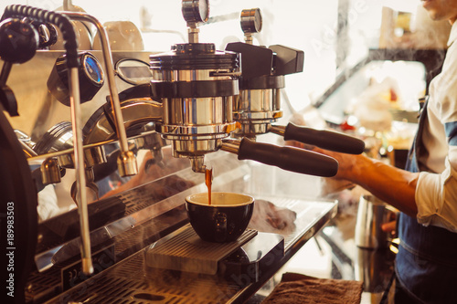 barista make coffee latte art with coffee espresso machine in coffee shop cafe in vintage color tone