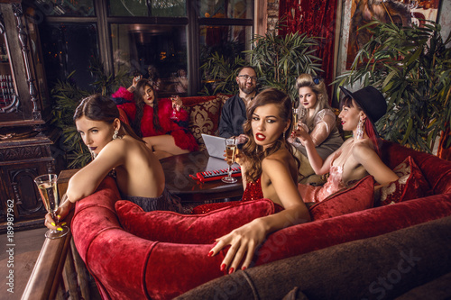 Photographie  Group of young stylish people dressed classical style in interior of luxury club