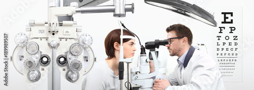 Fotografía  optometrist doing eyesight with woman patient measurement with slit lamp on whit