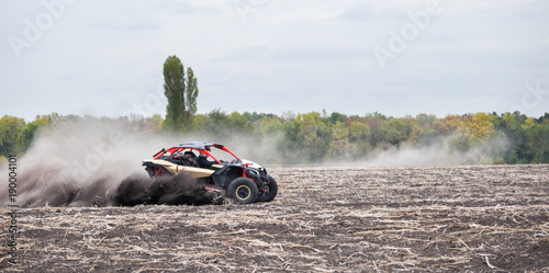 Fotografía  Quad bike quickly rides in dust clubs over plowed field