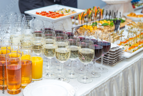 Poster Buffet, Bar Catering table with alcoholic and non-alcoholic drinks, dishes and snacks food on the event. Service at business meeting, party, weddings. Selective focus, space for text.